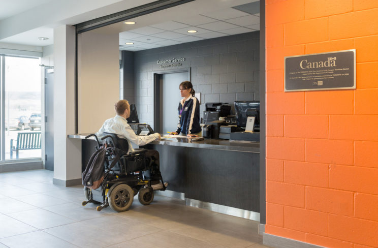 a man in a mobility device speaks with an agent at a customer service desk