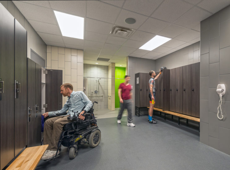 a man in a mobility device uses a locker in a change room
