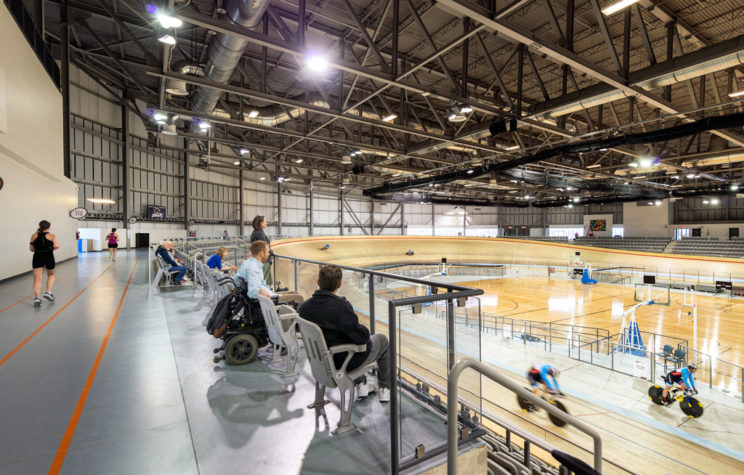 spectators watch from the viewing gallery as cyclists race on an indoor wooden track