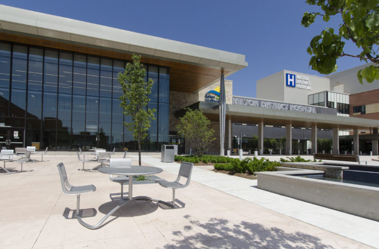 The entrance to the Milton District Hospital with accessible cafe tables in a paved area to the right of the entrance