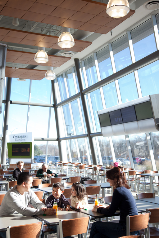 a family with two young children stop for a drink in a dining area with lots of natural light from the double-height, full glazing
