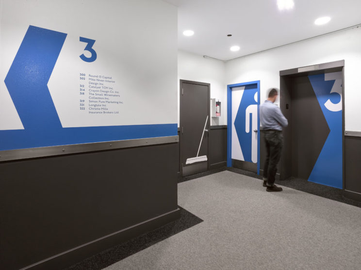 large, bold blue graphic signage on the walls, doors, and elevators identifying directions and room uses on the third floor of 100 Broadview
