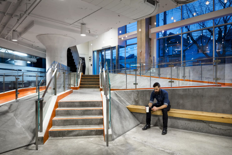 a man sits on a wooden bench in a raw concrete lobby with bright orange access ramps