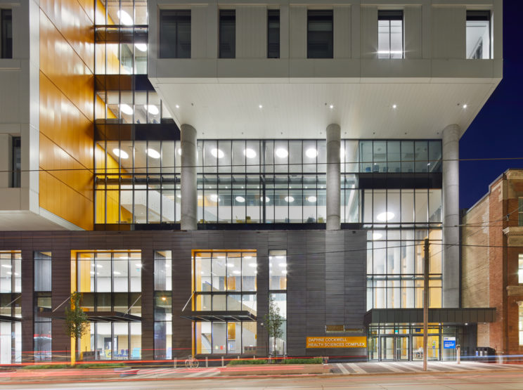 entrance to the Daphne Cockwell Health Sciences Complex at Ryerson University, a modern building with boxy grey, yellow and white sections and glazing in between