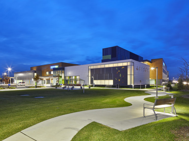 exterior at dusk of ErinoakKids Centre for Treatment and Development showing paved pathway leading across the grounds to the building entrance