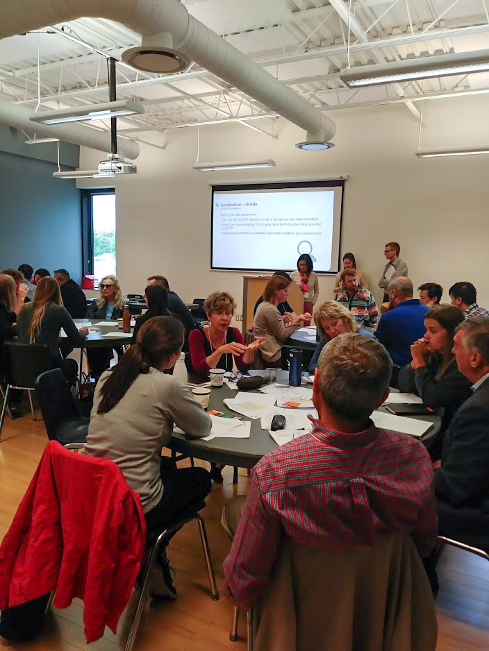 people sitting around three tables engaging in discussion, with a powerpoint on a projector in the background and Human Space staff at the front of the room