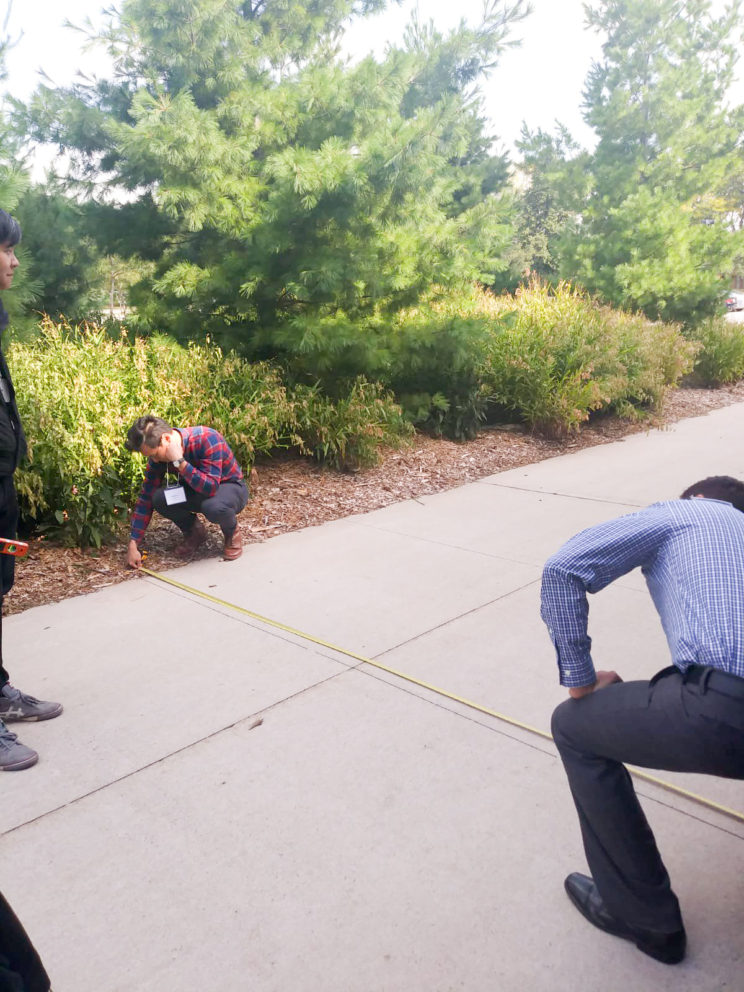 two men using a measuring tape to measure the width of a sidewalk