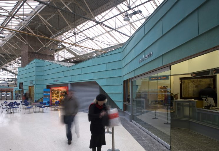 an older woman aproaches the Travel Centre kiosk in a train station with visible skylight and aqua coloured wall panelling and a cafe in the background