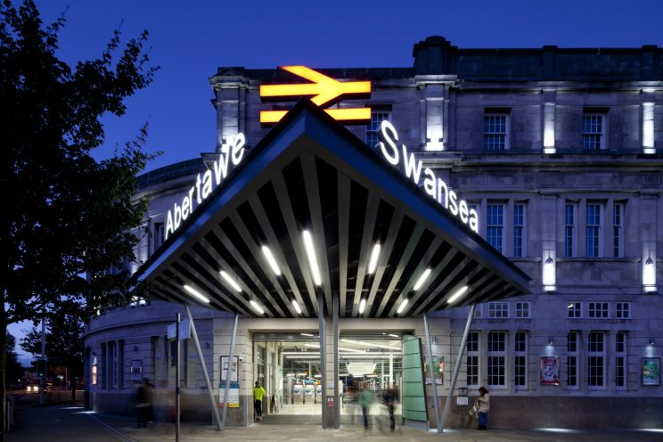 entrance of the Swansea train station in Wales at dusk, showing a triangluar awning with bold signage projecting over the brighly lit entrance doors