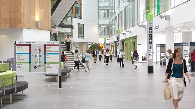 people walking through the lobby of a hospital with lots of natural light, wood materials and green accents and bright, large clear signing and wayfinding elements