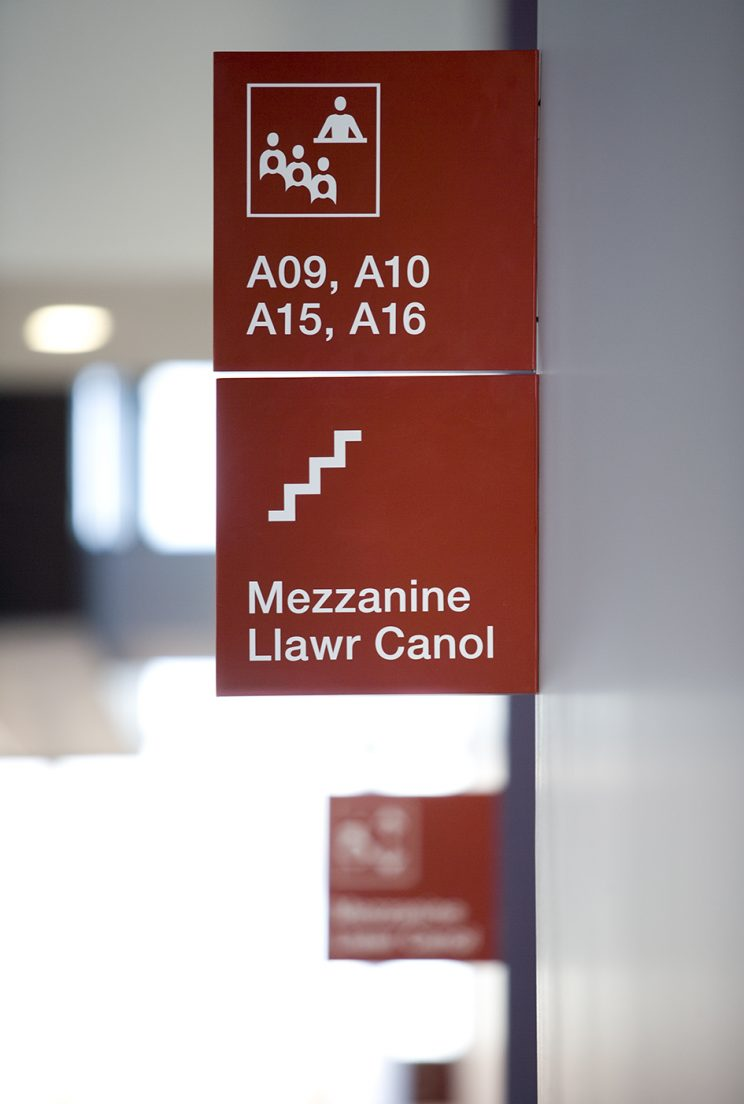 red signage with a symbol for starirs and the word Mezzanine in English and Welsh, and classroom numbers with an icon showing a teacher lecturing to students
