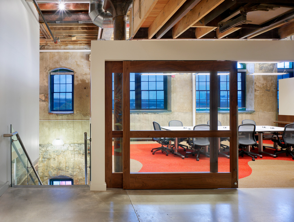 A boardroom with sliding glass doors framed in wood, in a converted heritage factory building with concrete floors, exposed stone walls and exposed wood ceiling