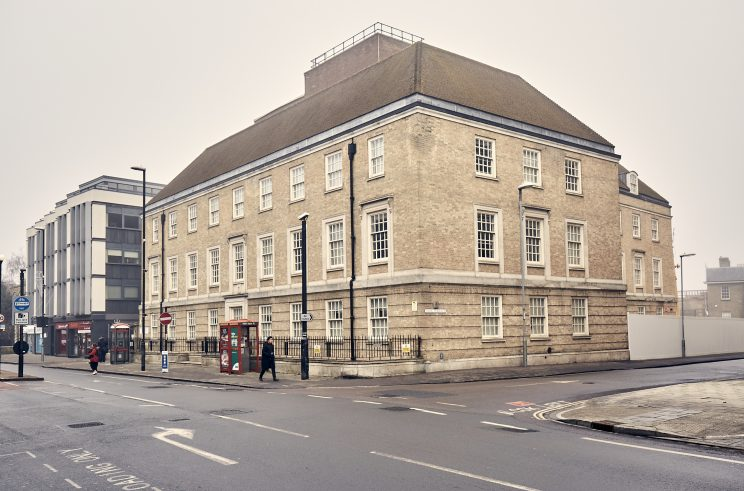 a 1920s-era British light stone coloured heritage building of three or four storeys