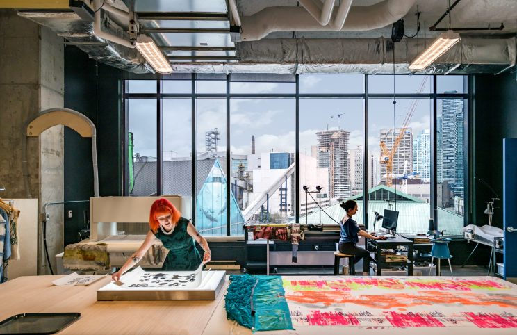 woman with bright orange hair lays out a screenprinting project in a workshop with lots of natural light and high ceilings