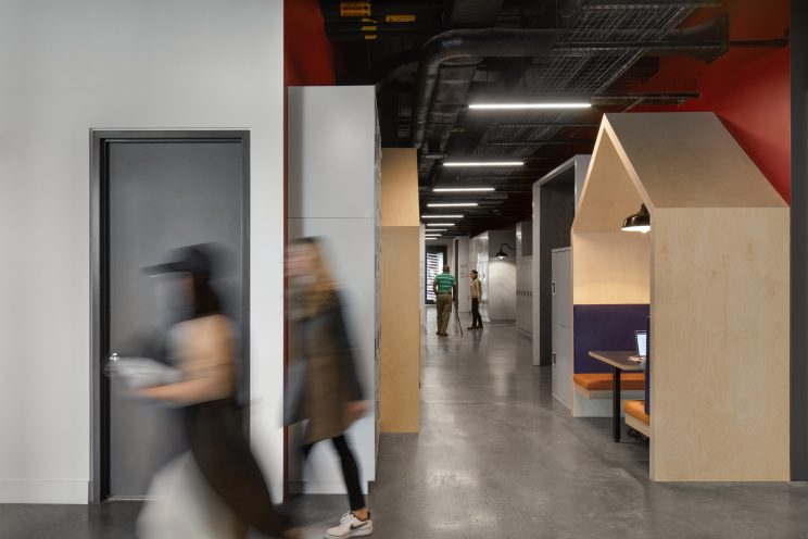 people walk in a hallway with wooden covered seating nooks