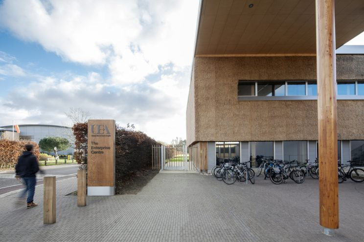 a person walks by a three-storey building with straw-coloured thatched cladding facade and cantilevered wood awning covering bicycle parking