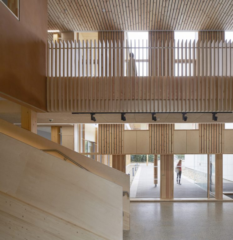 inside a building atrium with all-wood interiors: ceiling, staircase, mezzanine and walls.