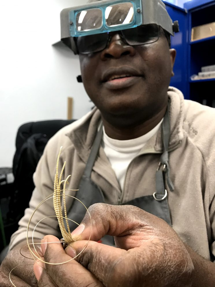 Patrick Missodey wearing safety goggles and manipulating some wire and jewellery making materials with his hands