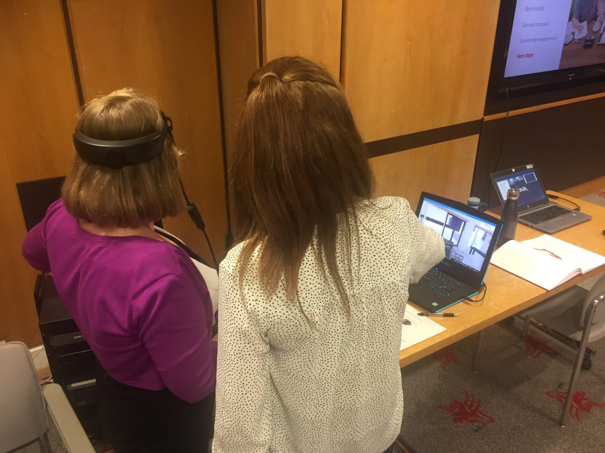 a woman seated wearing a virtual reality headset while another woman watches