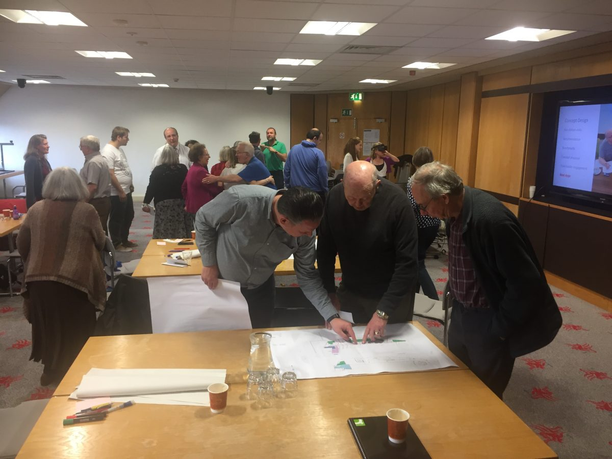 many people mingling and discussing and looking at documents in a seminar room