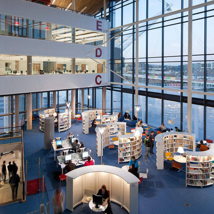 view from a mezzanine of a university library with half circle bookshelves and triple height floor to ceiling windows