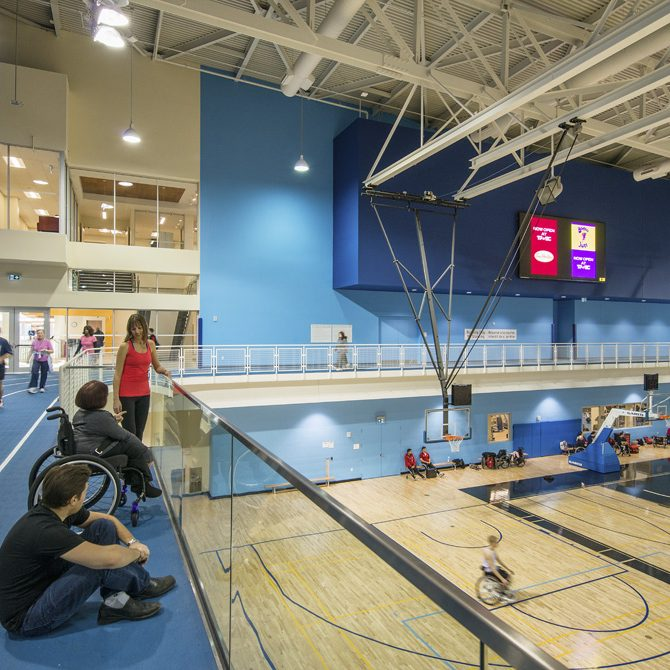 people watch a wheelchair basketball game from an elevated viewing gallery as people run on the adjacent indoor track