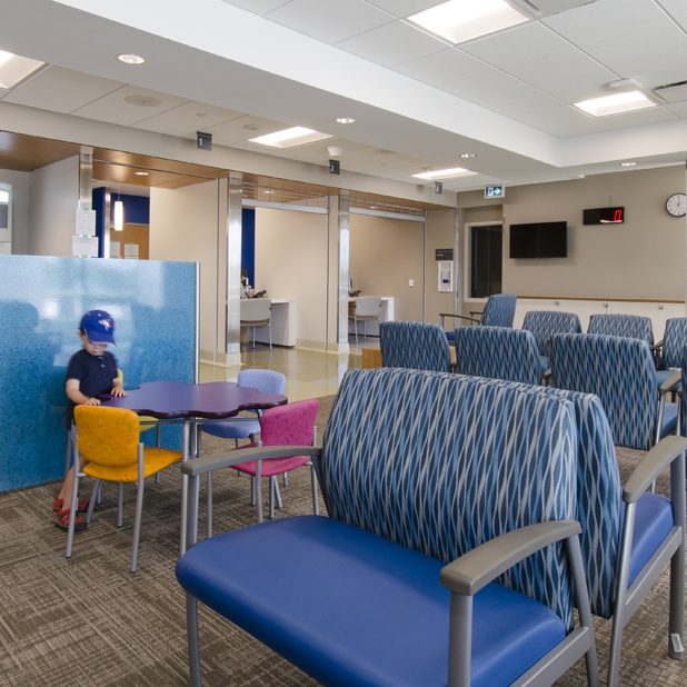 a little boy plays at a child-sized purple table with colourful chairs in a hospital waiting area with some double-wide seating in the foreground