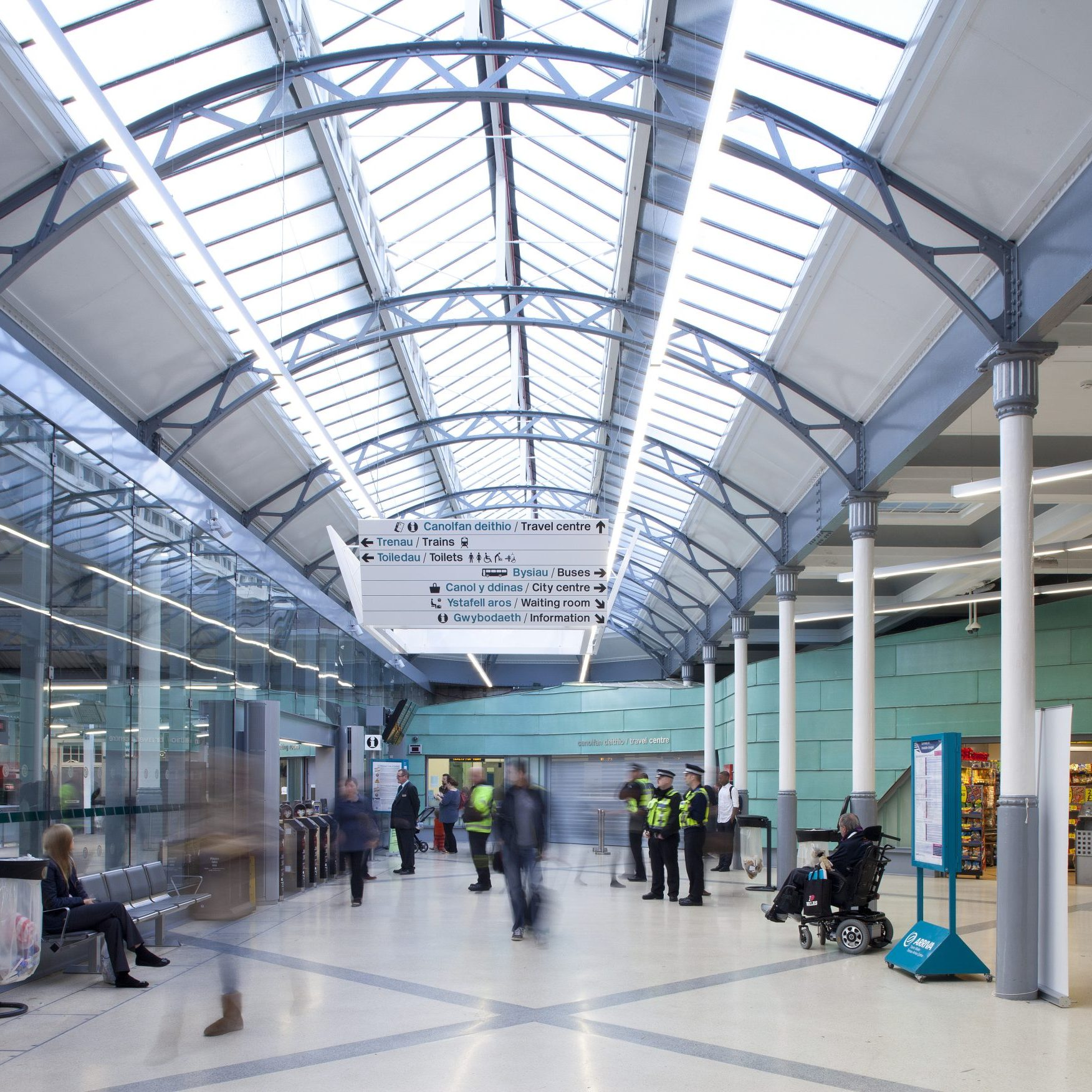 inside a train station with high arched ceilings with skylight and aqua wall cladding